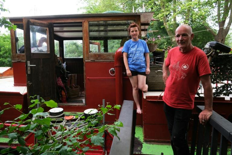 Emma Tissier, graphic designer, and her partner Caspar Galsworthy, craftsman, pose aboard their barge at the Port-Sud harbor, on the Canal du Midi in Ramonville, near Toulouse, southern France