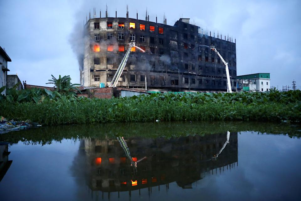 Flames rise the morning after a fire broke out at a factory on the outskirts of Dhaka, Bangladesh (Reuters)
