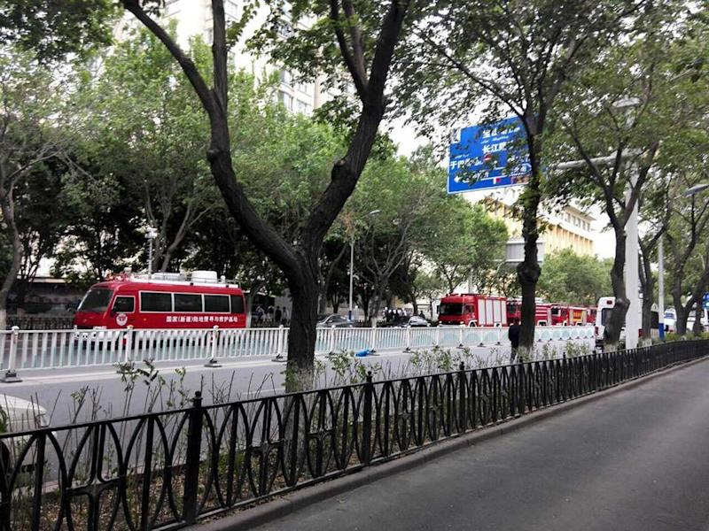 Fire trucks are seen on a street near the site where attackers ploughed two vehicles into a market and threw explosives, killing at least 31 people, in Urumqi in China's Xinjiang region on May 22, 2014 (AFP Photo/)