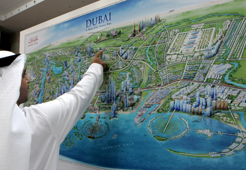 FILE - In this file photo dated Tuesday, Oct. 7, 2008, An Emirati man examines a graphic city map of Dubai, depicting new real estate developments, during an exhibition entitled Cityscape exhibition in Dubai, United Arab Emirates. It suddenly seems like Dubai is rediscovering its old habits. That means breathless hype is now back in vogue. Construction plans are again peppered with superlatives. (AP Photo/Kamran Jebreili, File)
