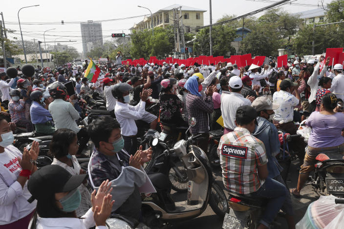 Motorist applaud while students march during a street march in Mandalay, Myanmar, Friday, Feb. 26, 2021. In the country's second-largest city, anti-coup protesters took to the streets Friday. By midday, security forces had blocked the main road in downtown Mandalay to prevent the protesters from gathering. (AP Photo)