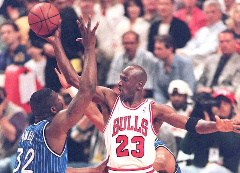 6d1c187ba50a Michael Jordan of the Chicago Bulls (R) passes the ball off under pressure  from