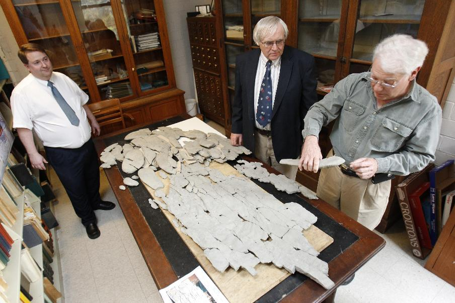 """In this April 20, 2012, photo, amateur paleontologist Ron Fine, of Dayton, Ohio, discusses the fossil he discovered with Carl Brett, center, and David Meyer, professors of Geology at the University of Cincinnati, at Caster Library on the campus in Cincinnati. Experts in the U.S. are trying to figure out what the 450 million-year-old fossil dubbed """"Godzillus"""" used to be. The 150-pound fossil recovered last year in Kentucky is more than 6 feet long. (AP Photo/The Cincinnati Enquirer, Gary Landers) MANDATORY CREDIT; NO SALES"""