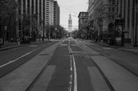 Market Street is mostly empty with the Ferry Building in the background in San Francisco on April 17, 2020. Normally, the months leading into summer bring bustling crowds to the city's famous landmarks, but this year, because of the coronavirus threat they sit empty and quiet. Some parts are like eerie ghost towns or stark scenes from a science fiction movie. (AP Photo/Eric Risberg)