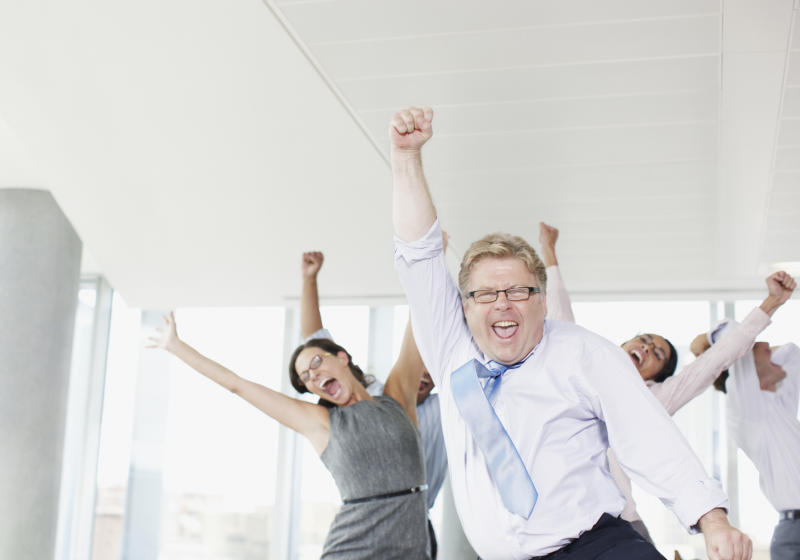 Businesspeople cheering with their hands in the air.