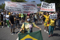 Supporters of Brazilian President Jair Bolsonaro protest the start of a 10-day period of increased restrictions, which includes Holy Week, to help curb the spread of COVID-19, on Copacabana beach in Rio de Janeiro, Brazil, Friday, March 26, 2021. (AP Photo/Silvia Izquierdo)