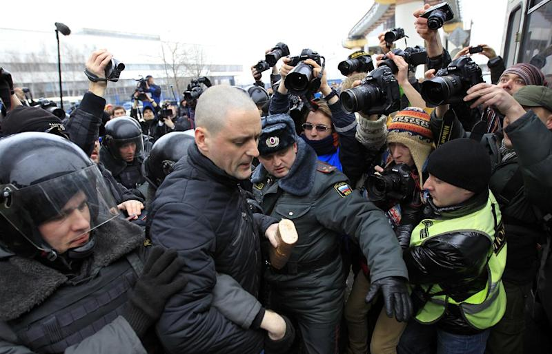"""In this Sunday, March 18, 2012 photo, police officers detain Sergei Udaltsov outside the Kremlin-loyal NTV television station,  in Moscow.  Russian opposition and human rights groups on Monday, Nov. 19, 2012,  urged Western consumer products giants to stop """"financing politically motivated persecution"""" by advertising on a Kremlin-friendly TV network known for its biased coverage of government critics and demonstrations against President Vladimir Putin. In the wake of unprecedented anti-Putin protests that followed last December's rigged parliament vote and Putin's return to the Kremlin in May, NTV has run dozens of news reports, talk shows and pseudo-documentaries accusing opposition leaders of plotting coups and terrorist attacks, of receiving money from Western governments, and of hiring migrant workers and neo-Nazis to participate in anti-Putin rallies.  (AP Photo/Sergey Ponomarev)"""