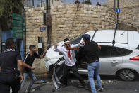 A Jewish driver, center, scuffles with Palestinians after he was attacked by Palestinian protesters near Jerusalem's Old City. Monday, May 10, 2021. Israeli police clashed with Palestinian protesters at a flashpoint Jerusalem holy site on Monday. (AP Photo/Ohad Zwigenberg)