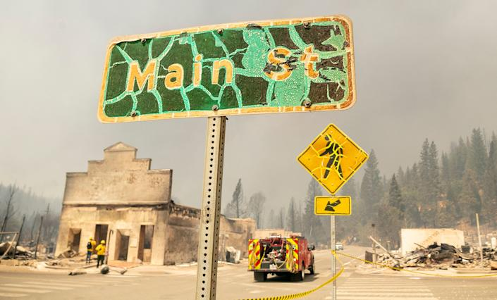 A fire-damaged street sign marks Main Street in a decimated downtown Greenville, California.