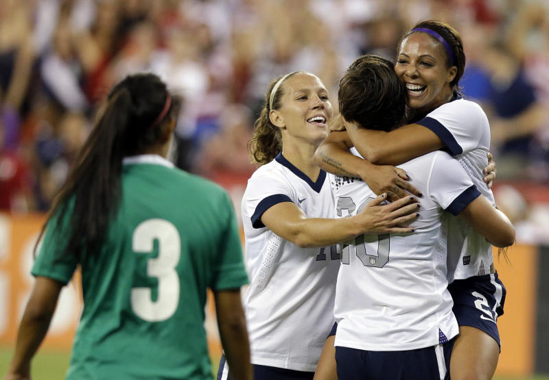 Mexico's defender Bianca Sierra (3) watches as United States midfielder Lauren Holiday (12), forward Abby Wambach (20) and forward Sydney Leroux (2) celebrate Leroux's first goal in the first half of an international friendly soccer match at RFK Stadium Tuesday, Sept. 3, 2013, in Washington. (AP Photo/Alex Brandon)
