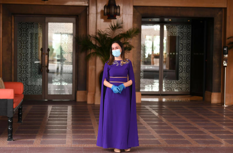Image: A mask-and-glove-clad staff member of the Jumeirah al-Naseem hotel waits at the hotel reception in Dubai (Karim Sahib / AFP - Getty Images)