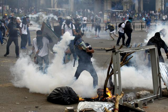 An anti-government protester throws a gas canister back at police during riots at Altamira square in Caracas March 6, 2014. A Venezuelan soldier and a motorcyclist died in a confused melee sparked by the opposition's barricading of a Caracas street, officials said on Thursday, boosting the death toll from nearly a month of violence to 20. Demonstrators have for weeks staged rallies and set up barricades to demand the resignation of President Nicolas Maduro, leading to clashes with security forces and government supporters. REUTERS/Carlos Garcia Rawlins (VENEZUELA - Tags: POLITICS CIVIL UNREST)