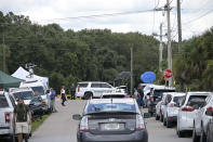 """Vehicles from members of the media and curious passersby line a road outside the entrance of the Carlton Reserve during a search for Brian Laundrie, Tuesday, Sept. 21, 2021, in Venice, Fla. Laundrie is a person of interest in the disappearance of his girlfriend, Gabrielle """"Gabby"""" Petito. (AP Photo/Phelan M. Ebenhack)"""