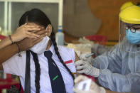 A teenager reacts as she receives a shot of the Sinovac vaccine for COVID-19 during a vaccination campaign at a school in Denpasar, Bali, Indonesia on Monday, July 5, 2021. (AP Photo/Firdia Lisnawati)