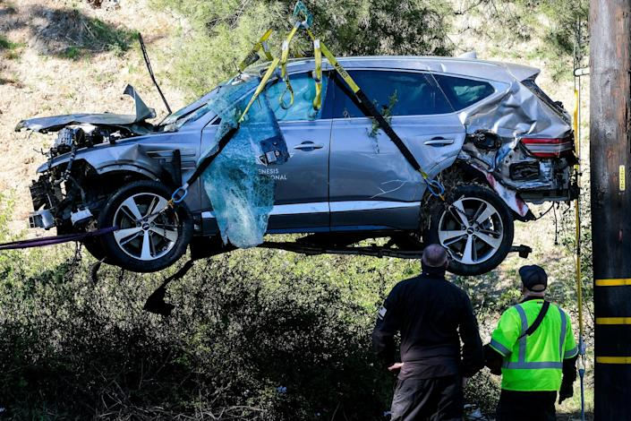 A crane lifts a vehicle after a rollover accident involving golfer Tiger Woods on Feb. 23 in the Rancho Palos Verdes section of Los Angeles.