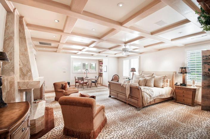 """<p>The master suite also has a large marble fireplace (left) and a sitting room (background). (All photos via <a href=""""http://bit.ly/1OjQdjg"""" rel=""""nofollow noopener"""" target=""""_blank"""" data-ylk=""""slk:Concierge Auctions listing"""" class=""""link rapid-noclick-resp"""">Concierge Auctions listing</a>)<br></p>"""