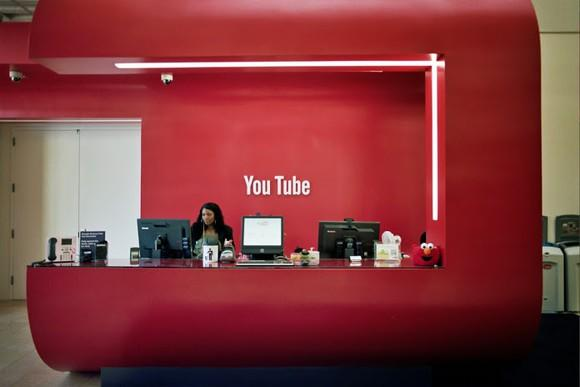 A bright red office lobby with the YouTube logo in white on the wall.