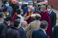 An attendant monk adjusts the face mask on Tibetan spiritual leader the Dalai Lama as he arrives at the Zonal Hospital to receive a COVID-19 vaccine in Dharmsala, India, Saturday, March 6, 2021. Medical officers confirmed that the Tibetan leader got the Covishield vaccine and is not showing any adverse reaction to the vaccine. (AP Photo/Ashwini Bhatia)