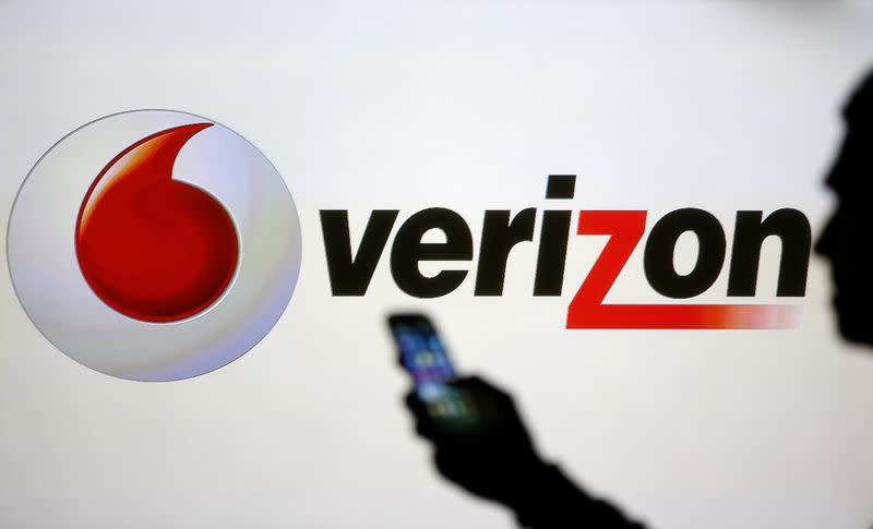 A man is silhouetted against a video screen with Vodafone and Verizon logos as he poses with a Samsung Galaxy S3 in this photo illustration taken in the central Bosnian town of Zenica in this file photo