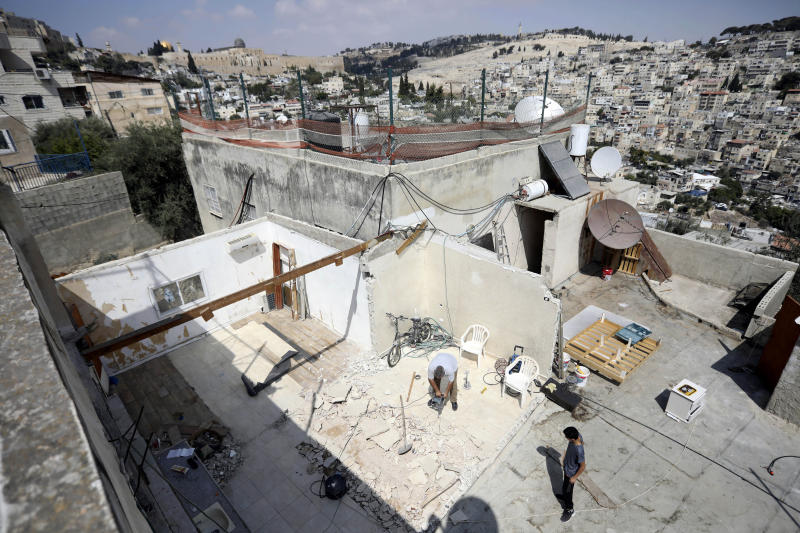 In this Monday, Sept. 9, 2019 photo, Palestinian Jamil Masalmeh uses a power tool to destroy an apartment he had added to his home years earlier, in the Silwan neighborhood of east Jerusalem. When he failed to secure a permit, Israeli municipal authorities gave him the option of destroying it himself or paying more than $20,000 for the city to demolish it. New data shows a spike in Jewish settlement construction in Israeli-annexed east Jerusalem since President Donald Trump took office and a huge, decades-old gap in the number of building permits granted to Jewish and Palestinian residents. (AP Photo/Mahmoud Illean)