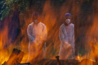 Relatives in protective suits stand next to the burning pyre of a person who died of COVID-19, at a crematorium in Srinagar, Indian controlled Kashmir, Tuesday, May 25, 2021. (AP Photo/Dar Yasin)