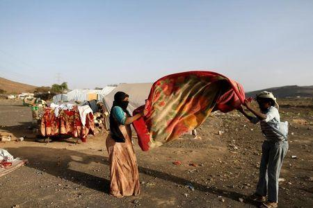People shake a blanket to rid it of dust at a camp for people displaced by the war near Sanaa, Yemen April 24, 2017. REUTERS/Khaled Abdullah