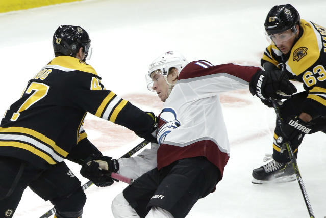 Boston Bruins' Torey Krug, left, and Brad Marchand, right, grapple with Colorado Avalanche's Matt Calvert, center, during the first period of an NHL hockey game, Sunday, Feb. 10, 2019, in Boston. The Bruins won 2-1 in overtime. (AP Photo/Steven Senne)