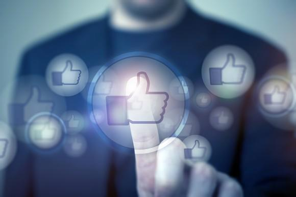 """A man pushing a digitally illustrated thumbs up button, depicting """"liking"""" content on Facebook."""