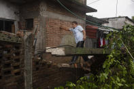 A man inspects the damage after a part of his home was toppled by the winds drought on by Hurricane Grace, in Tecolutla, Veracruz State, Mexico, Saturday, Aug. 21, 2021. Grace hit Mexico's Gulf shore as a major Category 3 storm before weakening on Saturday, drenching coastal and inland areas in its second landfall in the country in two days. (AP Photo/Felix Marquez)
