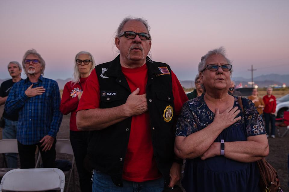 Trump supporters sing a patriotic song as they gather to watch the last presidential debate outside the Great American Pizza and Subs restaurant in Golden Valley, Arizona on October 22, 2020. (Photo by ARIANA DREHSLER / AFP) (Photo by ARIANA DREHSLER/AFP via Getty Images)