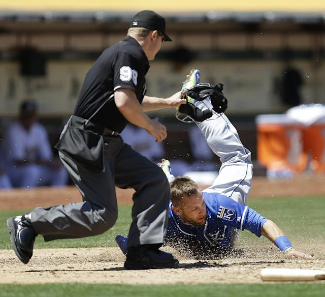 Kansas City Royals' Alex Gordon falls in front of home plate umpire Toby Basner, left, after being tagged out at home plate by Oakland Athletics catcher Derek Norris in the fourth inning of a baseball game Saturday, Aug. 2, 2014, in Oakland, Calif. (AP Photo/Ben Margot)