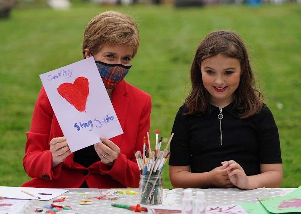 Carley-Jo and the First Minister held up her painting urging people to stay safe (Andrew Milligan/PA) (PA Wire)