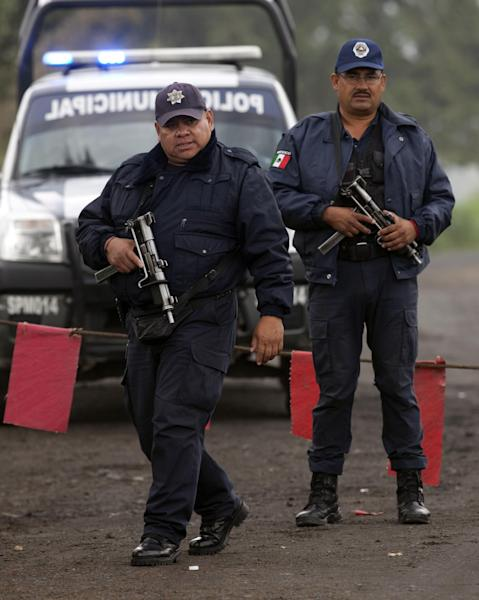 Municipal police guard the entrance to Rancho La Mesa where a mass grave was found in the municipality of Tlalmanalco, Mexico, Thursday, Aug. 22, 2013. Mexican authorities said they found the mass grave east of Mexico City and are testing to determine if it holds some of the 12 people who vanished from a bar in an upscale area of the capital nearly three months ago. (AP Photo/Ivan Pierre Aguirre)