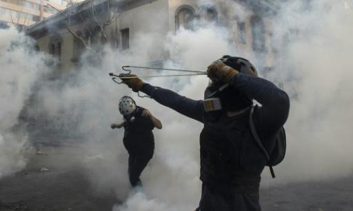 A demonstrator aims a sling at the police during a protest against Chilean President Sebastian Pinera's government in Santiago
