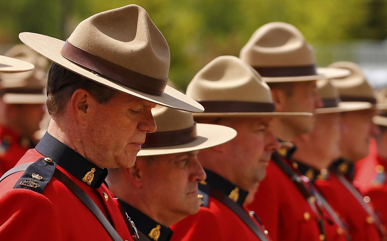 Royal Canadian Mounted Police officers gather to attend the funeral for three fellow officers who were killed last week in Moncton, New Brunswick, June 10, 2014. Justin Bourque, 24, was charged with murder on Friday in the slayings of the three Royal Canadian Mounted Police officers, Constables Fabrice Georges Gevaudan, 45; David Joseph Ross, 32, and Douglas James Larche, 40, during a shooting spree in the eastern Canadian city of Moncton. The shooting spree was one of the worst of its kind in Canada, where gun laws are stricter than in the United States and deadly attacks on police are rare. REUTERS/Mark Blinch (CANADA - Tags: CRIME LAW OBITUARY)