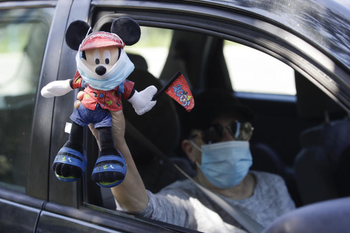A Disney employee carries a Mickey Mouse doll during a drive-by protest to demand a safe reopening amid the coronavirus pandemic Saturday, June 27, 2020, in Anaheim, Calif. Workers are demanding regular testing, stricter cleaning protocols and higher staffing levels. Disney had originally proposed reopening on July 17th but announced this week it was postponing. (AP Photo/Marcio Jose Sanchez)