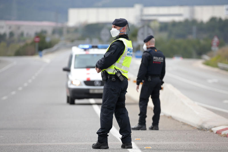 Police officers stand on the closed off road near Igualada, Spain, Friday, March 13, 2020. Over 60,000 people awoke Friday in four towns near Barcelona confined to their homes and with police blocking roads. The order by regional authorities in Catalonia is Spain's first mandatory lockdown as COVID-19 coronavirus infections increase sharply, putting a strain on health services and pressure on the government for more action. For most people, the new coronavirus causes only mild or moderate symptoms, such as fever and cough. For some, especially older adults and people with existing health problems, it can cause more severe illness, including pneumonia. (AP Photo/Joan Mateu)
