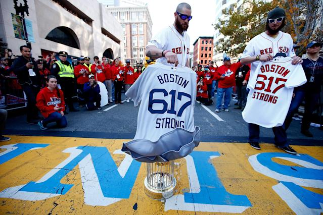 BOSTON, MA - NOVEMBER 02: Jonny Gomes #5 and Jarrod Saltalamacchia #39 of the Boston Red Sox lay the World Series trophy and the 'Boston Strong 617' jerseys onto the finish line of the Boston Marathon on Boylston Street during the World Series victory parade on November 2, 2013 in Boston, Massachusetts. (Photo by Jared Wickerham/Getty Images)