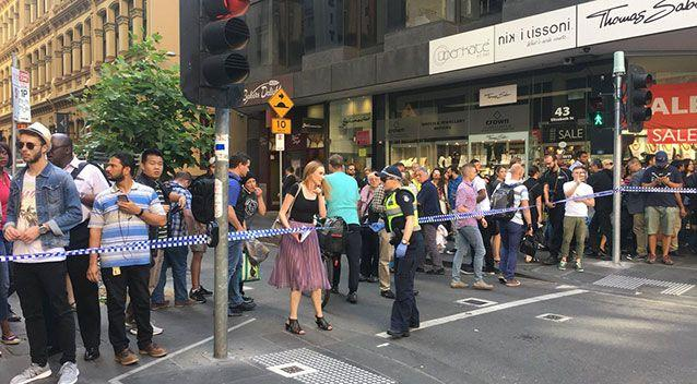 Pedestrians look on after at least 14 pedestrians were struck by a white 4WD. Source: 7 News