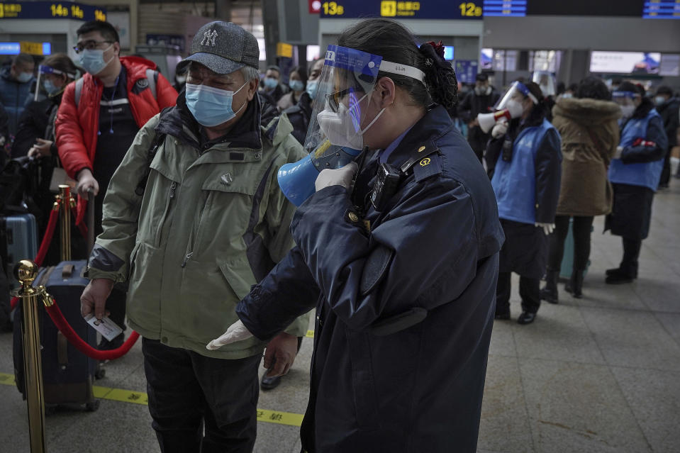 A worker wearing a face mask and face shield to help curb the spread of the coronavirus uses a loud speaker to ask a masked passenger to keep distancing in the line at the South Train Station in Beijing, Thursday, Jan. 28, 2021. Efforts to dissuade Chinese from traveling for Lunar New Year appeared to be working. Beijing's main train station was largely quiet on the first day of the travel rush and estimates of passenger totals were smaller than in past years. (AP Photo/Andy Wong)