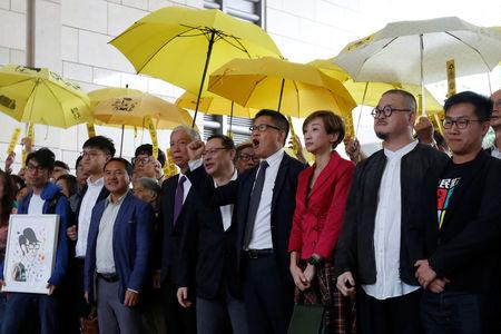 Pro-democracy activists pose outside a court in Hong Kong