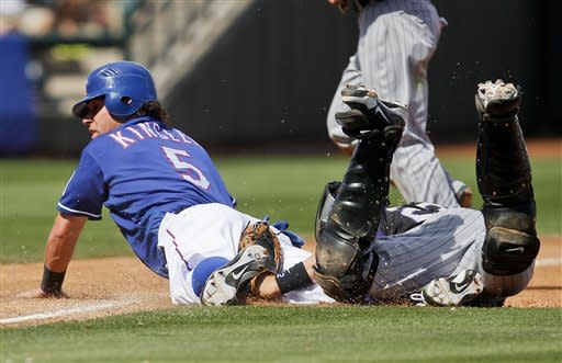 Texas Rangers' Ian Kinsler, left, is tagged out at third base by Colorado Rockies catcher Jordan Pacheco after being caught in a rundown after over-running the base in the third inning of a spring training baseball game on Wednesday, March 14, 2012, in Surprise, Ariz. (AP Photo/Lenny Ignelzi)