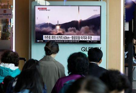 People watch a TV broadcasting a news report on North Korea's missile launch, at a railway station in Seoul