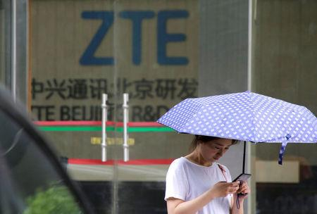 FILE PHOTO: A woman stands outside a building of ZTE Beijing research and development center in Beijing, China June 13, 2018. REUTERS/Jason Lee