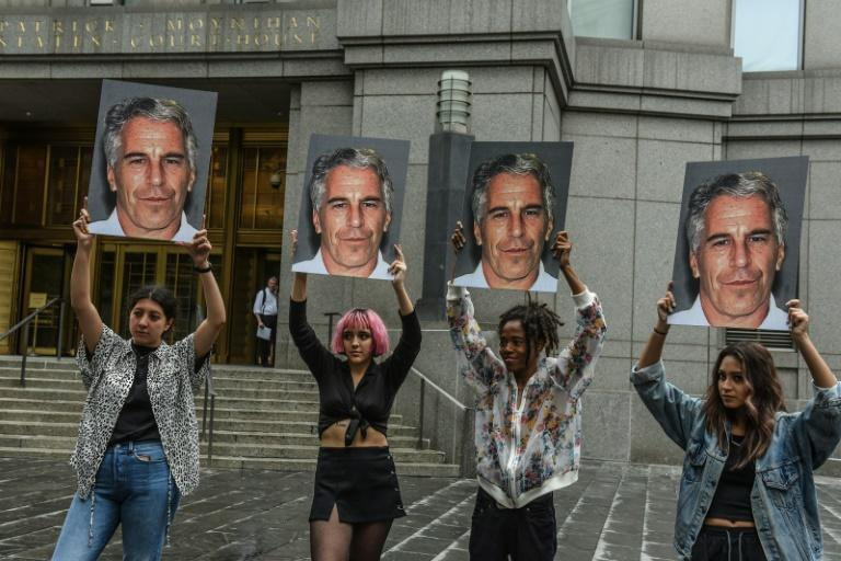 "Protest group called ""Hot Mess"" hold up photos of Jeffrey Epstein in front of the Federal courthouse in New York City (AFP Photo/STEPHANIE KEITH)"