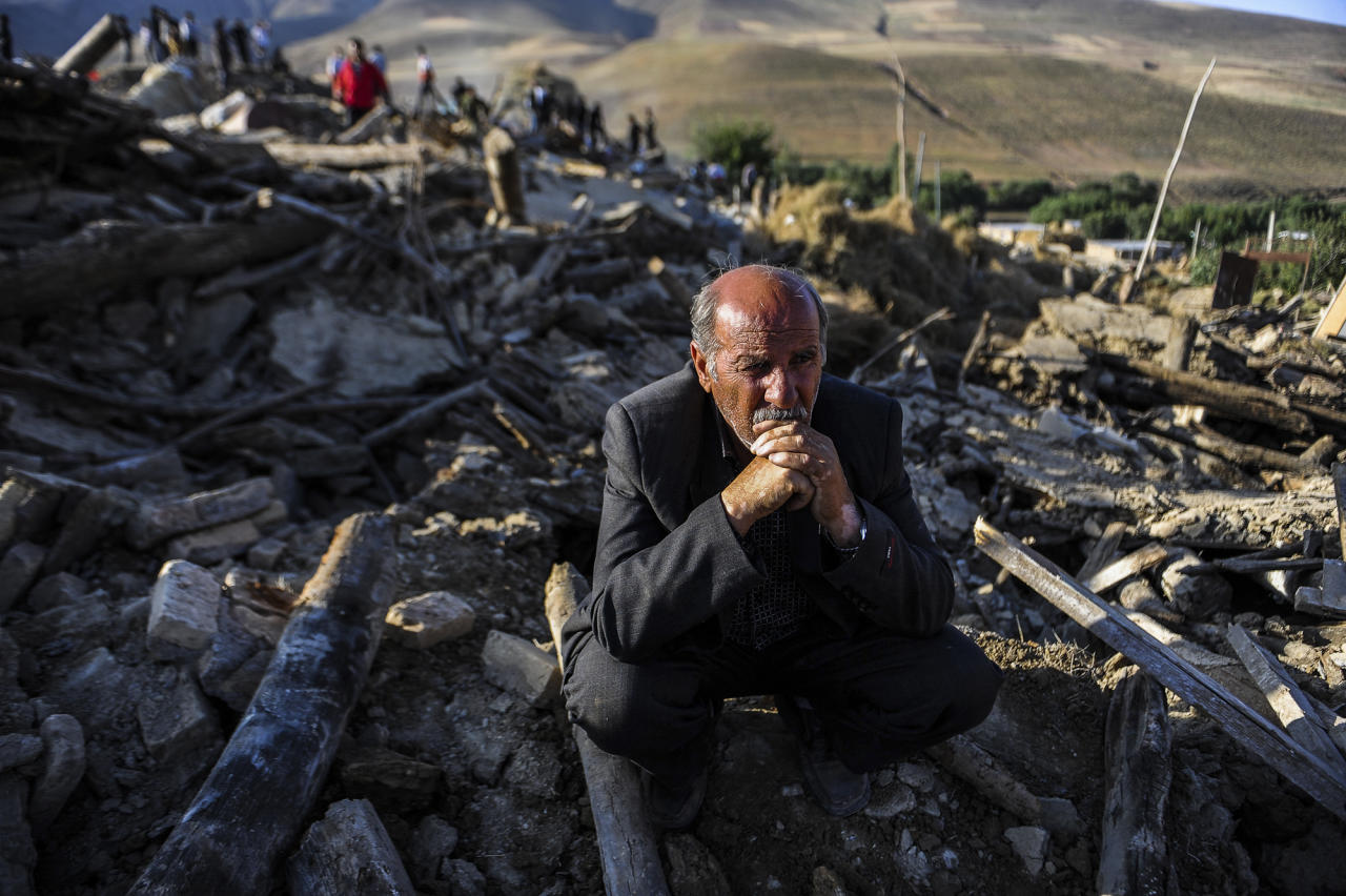A victim of Saturday's earthquake sits on the ruins of buildings at the village of Bajebaj near the city of Varzaqan in northwestern Iran, Sunday, Aug. 12, 2012. Twin earthquakes in Iran have killed at least 250 people and injured over 2,000, Iranian state television said on Sunday, after thousands spent the night outdoors after their villages were leveled and homes damaged in the country's northwest. Iran is located on seismic fault lines and is prone to earthquakes. It experiences at least one earthquake every day on average, although the vast majority are so small they go unnoticed. (AP Photo/ISNA, Ruhollah Vahdati)