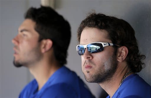 Kansas City Royals third baseman Mike Moustakas, right, and first baseman Eric Hosmer watch from the dugout during a spring training baseball game against the Milwaukee Brewers, Wednesday, Feb. 27, 2013, in Surprise, Ariz. (AP Photo/Charlie Riedel)