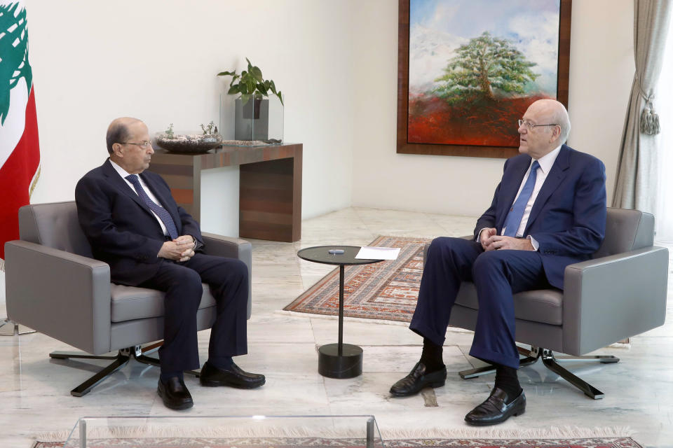 In this photo released by Lebanese government, Lebanese President Michel Aoun, left, meets with Prime Minister Najib Mikat, at the presidential palace, in Baabda, east of Beirut, Lebanon, Friday, Sept 10, 2021. Lebanese factions formed a new government on Friday, breaking a 13-month deadlock that saw the country slide deeper into financial chaos and poverty. (Dalati Nohra/Lebanese Official Government via AP)