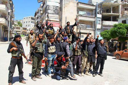 Rebel fighters celebrate with their weapons as they pose in Jisr al-Shughour town, after they took control of the area April 25, 2015.  REUTERS/Ammar Abdullah