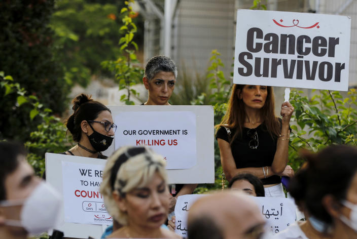 FILE - In this Aug. 26, 2021 file photo, cancer patients and supporters hold placards during a sit-in to protest shortages in medications, in front of the U.N. headquarters in Beirut, Lebanon. Amid a devastating economic crisis, Lebanon is grappling with severe shortages of medical supplies, fuel and other necessities, threatening treatment for tens of thousands of people. (AP Photo/Bilal Hussein, File)
